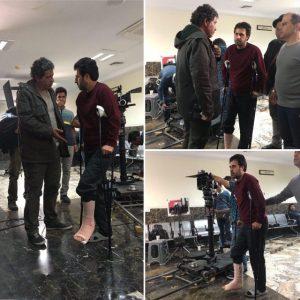 هومن حاجی عبداللهی با عصا سر صحنه فیلم برداری