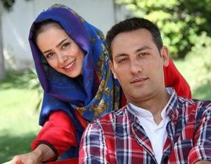 عکس دو نفره الناز حبیبی با شال آبی و مانتو قرمز و همسرش با لباس چهارخانه
