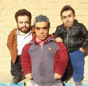 علی ابراهیمی بازیگر کوتاه قد سینمای ایران با کاپشن طوسی قرمز به همراه دوستانش