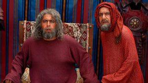 محمود جعفری در نقش معقل با لباس و شال قرمز رنگ