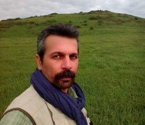 سلفی مجید پتکی در یک چمنزار با شال آبی دور گردنش