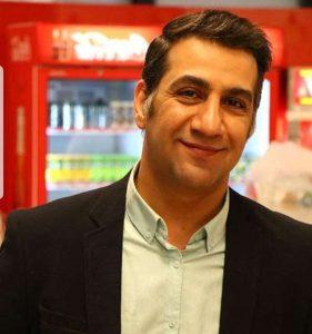 محمد نادری در یک سوپرمارکت با کت مشکی و پیراهن آبی