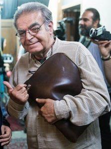 حمید لولایی با پیرهن کرمی و کیف چرم قهوه ای در صحنه ای از فیلمبرداری