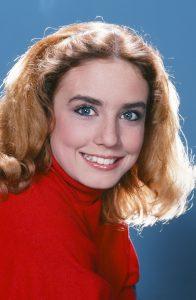عکس پرتره دانا پلاتو با لباس قرمز در حال لبخند زدن