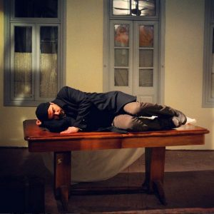 علی مصفا خوابیده روی یک میز در صحنه ای از فیلم در دنیای تو ساعت چند است