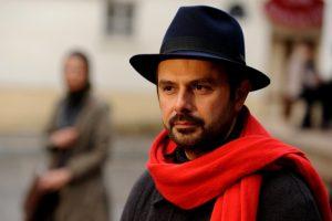 علی مصفا با شال قرمز و کلاه شاپوری در صحنه ای از فیلم در دنیای تو ساعت چند است