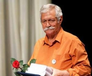 آتش تقی پور از بازیگران مرد قد بلند ایرانی با پیراهن نارنجی و گل و تقدیر نامه در دستش