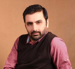 امین زندگانی از بازیگران مرد قد بلند ایرانی با پیراهن چهارخونه قرمز و ژیله قهوه ای