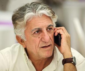 تیپ سفید رضا کیانیان در حال صحبت با موبایل
