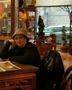 عکسی از مریم امیرجلالی با لباس مشکی و کلاه در یک کافه