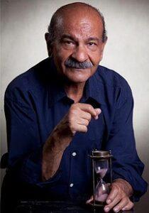 فردوس کاویانی با پیراهن ابی و یک ساعت شنی در دستش
