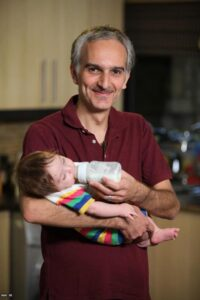 بیژن بنفشه خواه با تیشرت قرمز در حال شیر دادن به فرزندش
