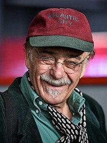 عکسی از رضا بابک با کلاه و پیراهن سبز و شال گردن