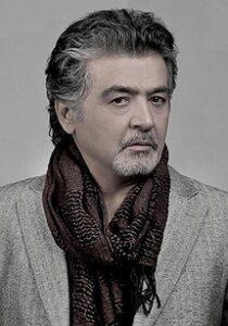 عکس سیاه سفید از رضا رویگری با کت و دستمال گردن