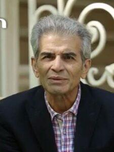 محمد شیری با لباس چهارخانه و کت مشکی