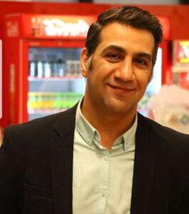 محمد نادری با کت مشکی و پیراهن سفید در یک سوپرمارکت