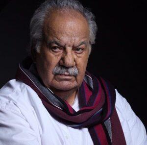ناصر ملک مطیعی با پیراهن سفید و شال راه راه زرشکی