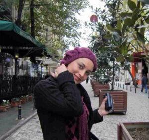 عکس مریم کاویانی با لباس مشکی و شال و کلاه بنفش در خارج از کشور