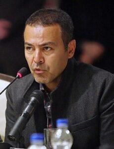 تیپ مشکی فریبرز عرب نیا در یک برنامه در حال سخنرانی