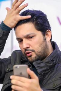 تیپ مشکی حامد بهداد با کاپشن در حال نگاه کردن در سلفی گوشی اپل اش