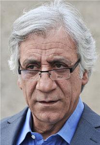 پرتره مسعود رایگان با پیراهنآبی و کت سفید