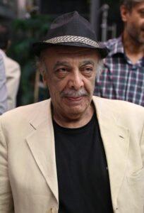 عباس محبوب با کت کرم و تیشرت و کلاه مشکی