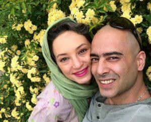 نیما فلاح با تیشرت طوسی و همسرش سحر ولدبیگی در کنار گلها