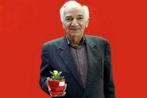 رضا بنفشه خواه با کت و شلوار مشکی و یک گلدان در دستش