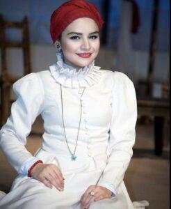 تینا عبدی با روسری قرمز و لباسی در صحنه تئاتر