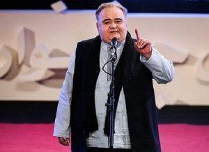 اکبر عبدی با جلیقه مشکی و پیراهن آبی از بازیگران مرد ایرانی بالای 40 سال