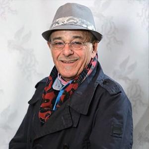 رضا بابک با پالتو و کلاه طوسی از بازیگران مرد ایرانی بالای 40 سال