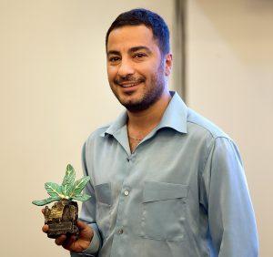 نوید محمدزاده با پیراهن طوسی و یک گل در دستش